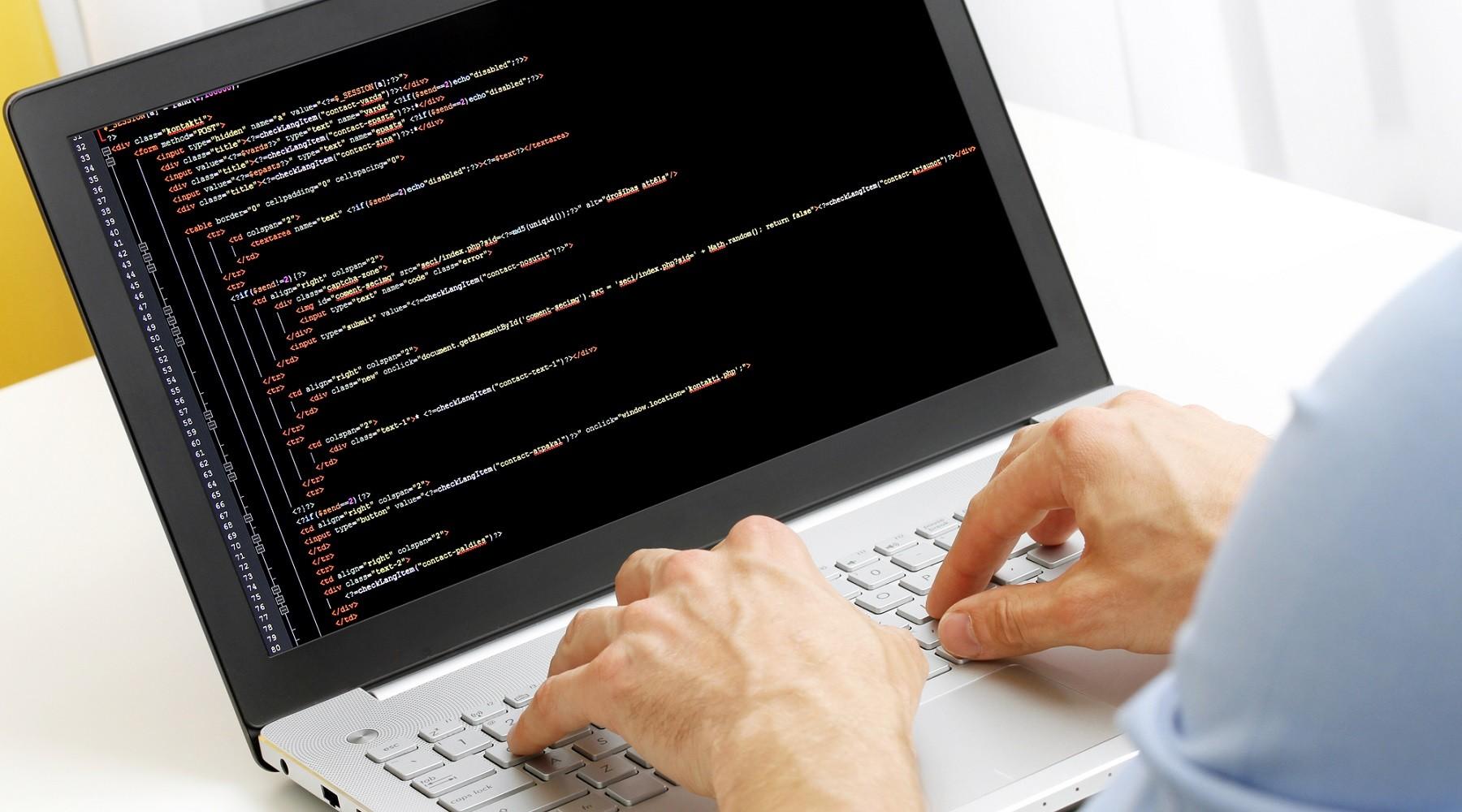 Vývojář píše na notebooku kód k softwaru.