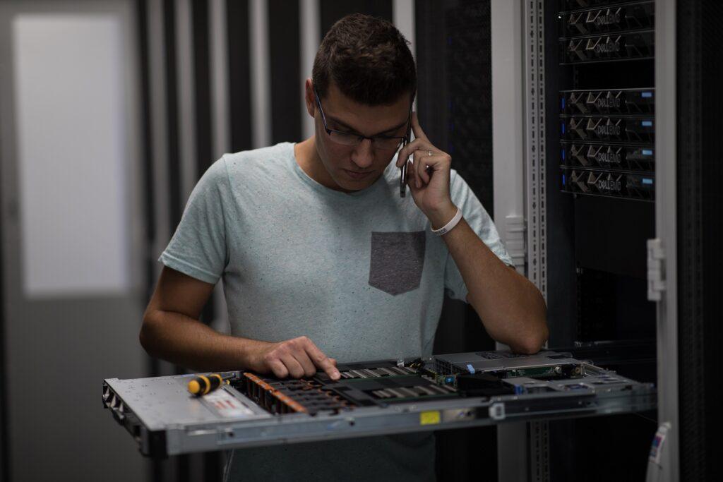 Technik v datacentru kontroluje server.