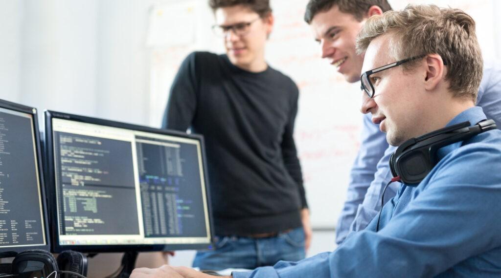 Tři mladi programátoři se dívají do monitorů