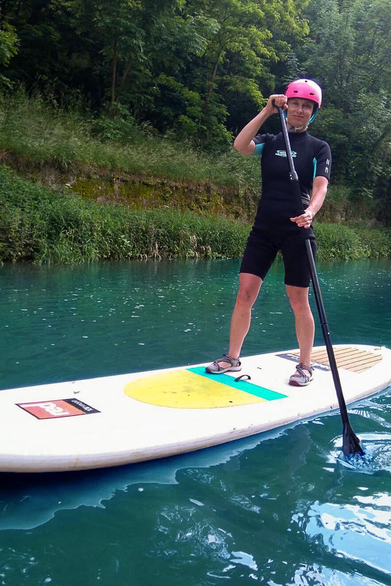 Fotografie Hany, která brázdí vody na paddleboardu.